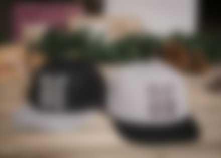 Selvdesignede baseballcapser ligger på gulvet foran julepynt