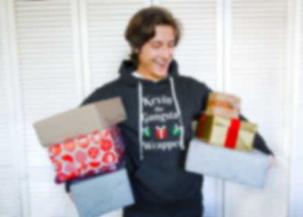 En mann holder gaver og har på en egendesignet hettegenser
