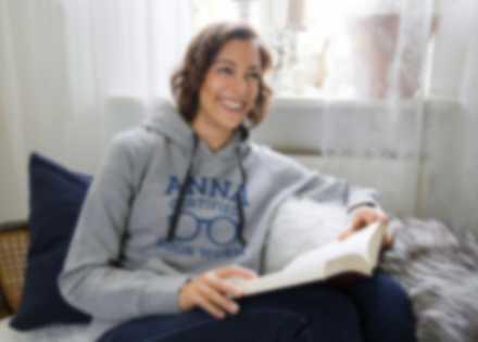 En kvinne leser en bok på sofaen og har på en personalisert genser