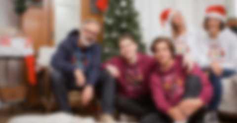 En familie poserer foran juletreet og har på seg personaliserte gensere