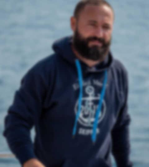 Segelcrew sitzt auf einem Schiff und trägt personalisierte T-Shirts, Hoodies und Caps