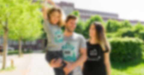 Foreldre og barn med egendesignede T-skjorter med individuelt motiv og tekst.