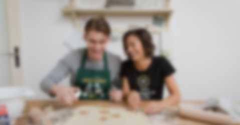Äiti ja poika leipomassa pipareita itse suunnitelluissa t-paidoissa ja essuissa, joissa on yksilöllinen design ja teksti.