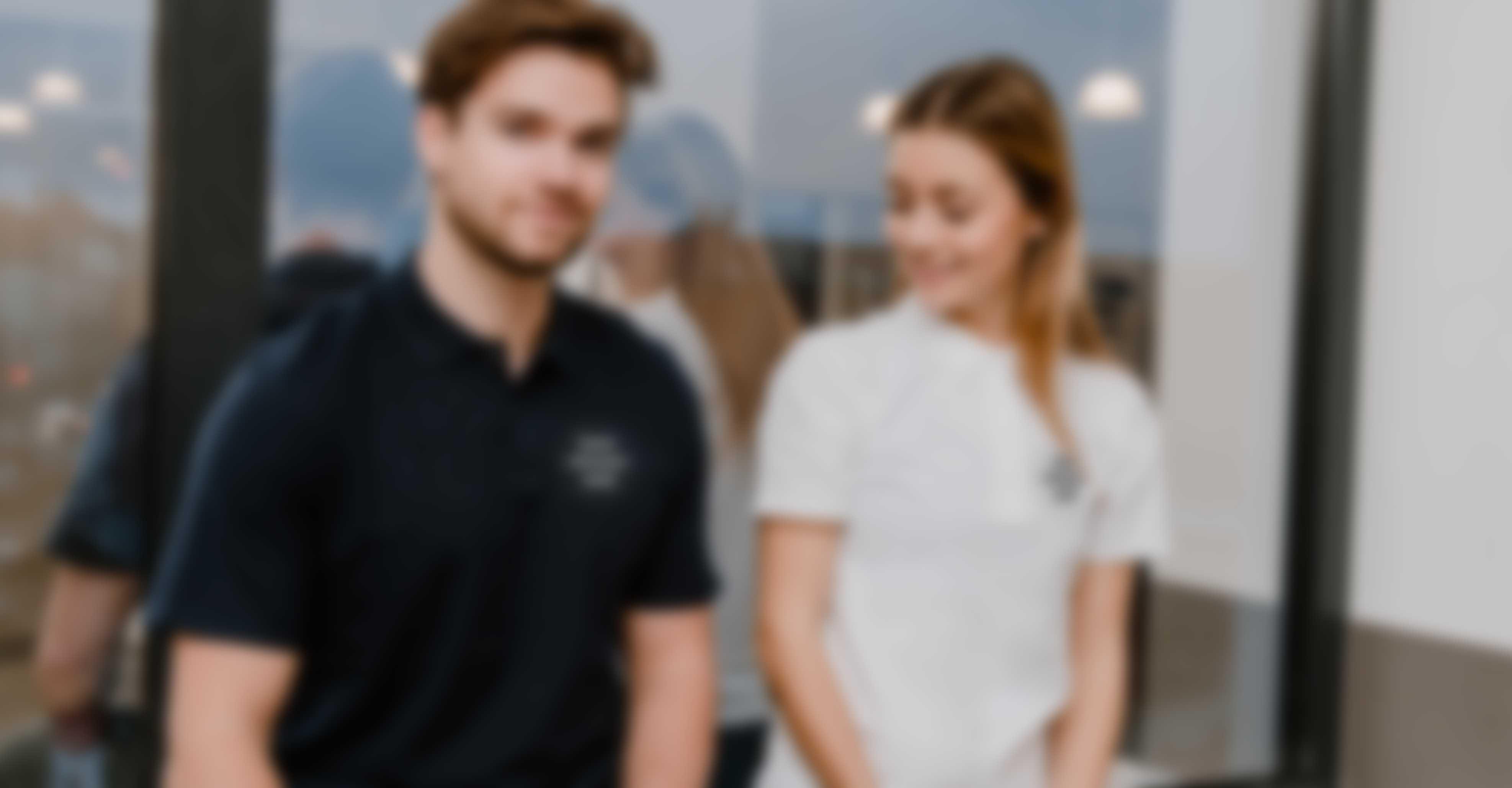 Junges Paar sitzt vor einem Fenster und trägt personalisierte Polo Hemden