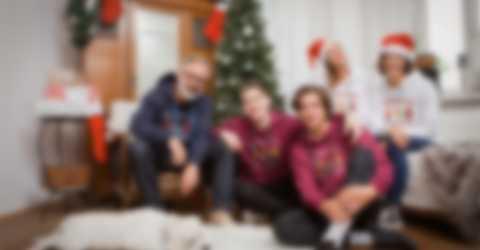 Familie posiert vor einem Weihnachtsbaum und trägt personalisierte Pullover
