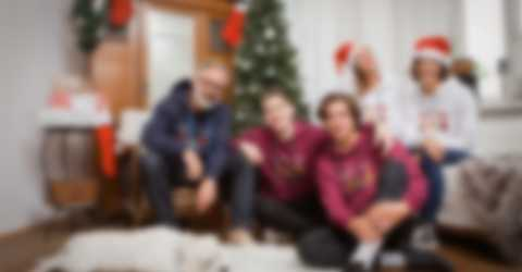 Une famille posant devant le sapin de Noël et portant un sweat-shirt à capuche personnalisé