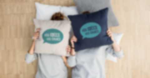 Deux femmes se cachent le visage derrière un coussin personnalisé