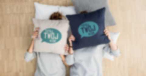 Dwie kobiety chowają twarze za samodzielnie zaprojektowanymi poszewkami na poduszki
