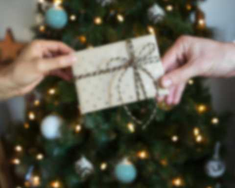 Two people exchanging gift voucher in front of Christmas tree.