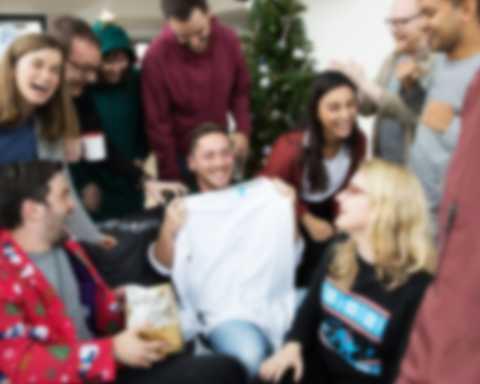 Mężczyzna trzyma w górze samodzielnie zaprojektowaną koszulkę z długim rękawem podczas imprezy bożonarodzeniowej z kolegami