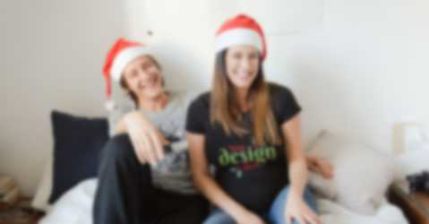 Man and woman wearing custom t-shirts sit and laugh together.