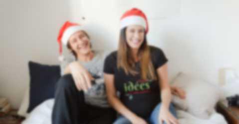 Couple portant un bonnet de Noël et un t-shirt personnalisable avec des designs et textes pour Noël.