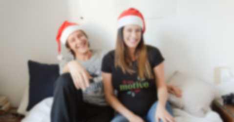 Coppietta con cappellino natalizio e maglietta personalizzata con un testo e un motivo natalizio scelti da loro.