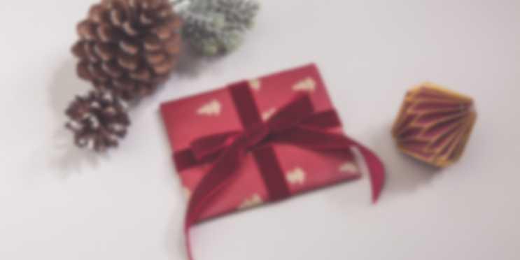 Et gavekort pakket inn som presang deles ut foran juletreet