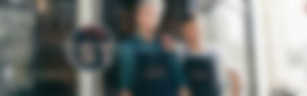 Due uomini fuori da un caffè che indossano grembiuli personalizzati con testo