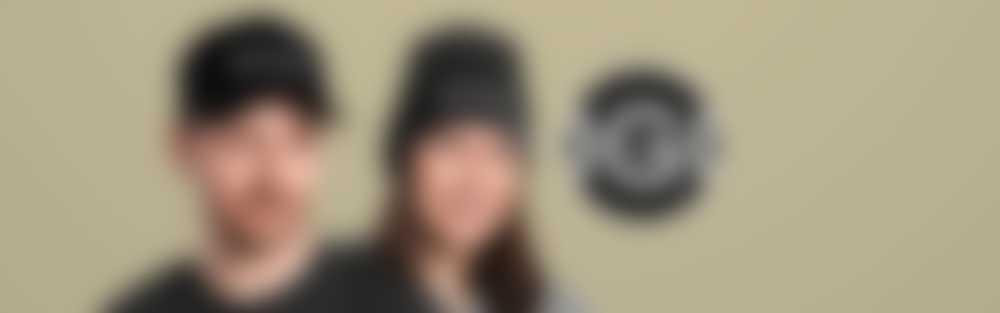 Kvinne med hette og kvinne med hatt med brodert tekst
