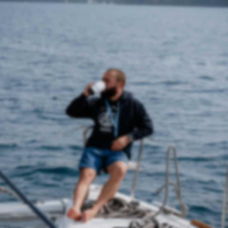 Kapitän trägt selbst gestalteten Hoodie und trinkt Kaffee