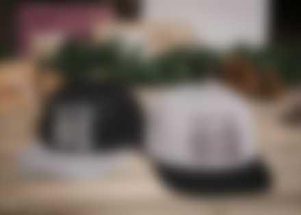 Selbst gestalte Basecaps liegen auf dem Boden vor Weihnachtsdekoration