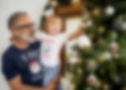 Grand-père porte son petit fils dans les bras. Ils décorent le sapin de Noël avec leur t-shirt personnalisé