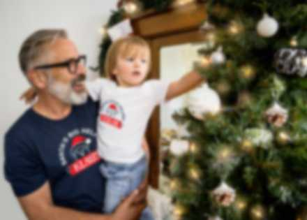 Man and grandchild admire Christmas tree while wearing custom t-shirts.