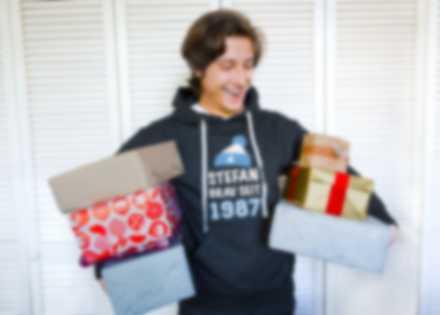 Mann hält Geschenke und trägt einen selbst gestalteten Hoodie