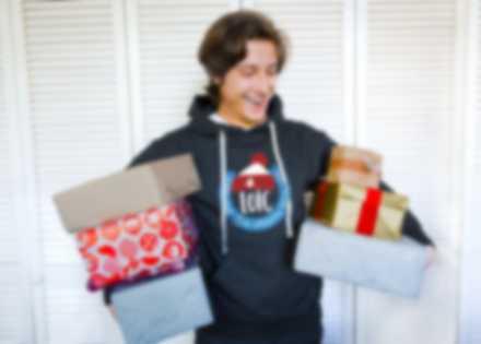 Un homme portant un sweat à capuche personnalisé et des cadeaux de Noël sous les bras