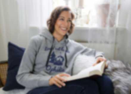 Une femme portant un sweat personnalisé et lisant un livre le sourire aux lèvres