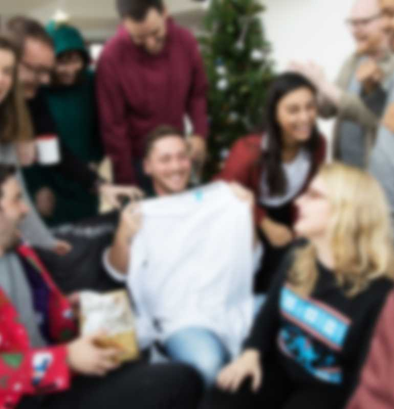 Man holding up custom long-sleeve shirt while surrounded by co-workers at Christmas party.