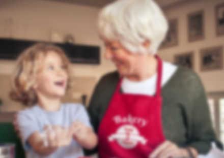 Mummi leipoo lapsenlapsen kanssa itse suunniteltu esiliina yllään