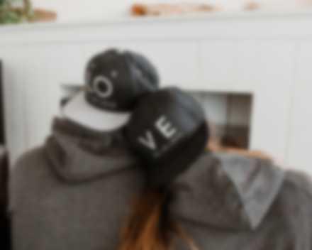 Un couple devant la télé porte des casquettes personnalisées