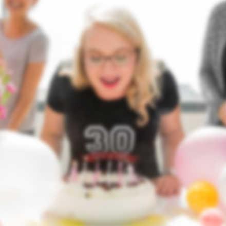 Dziewczynka zdmuchuje świeczki z urodzinowego tortu. Ma na sobie indywidualnie zaprojektowaną koszulkę, którą dostała w prezencie.