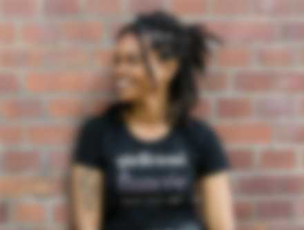 Woman standing against brick wall while wearing a customised t-shirt.