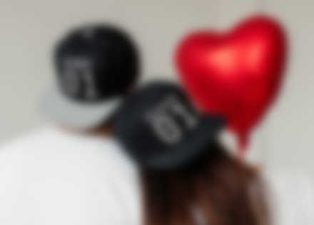 Paar trägt selbst gestaltete Caps mit Valentinstag Design.