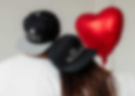 Couple wearing personalised caps with Valentine\'s design.