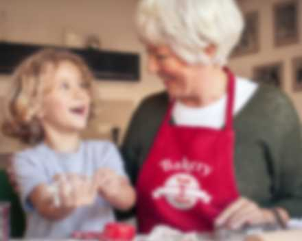Grandmother and child have fun in the kitchen while grandmother wears a personalised apron.