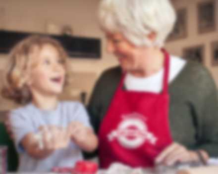 Großmutter trägt selbst gestaltete Schürze beim Backen mit ihrem Enkel