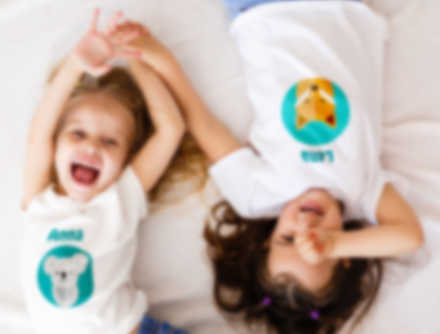 Two smiling children laughing in a bed while wearing customised t-shirts.