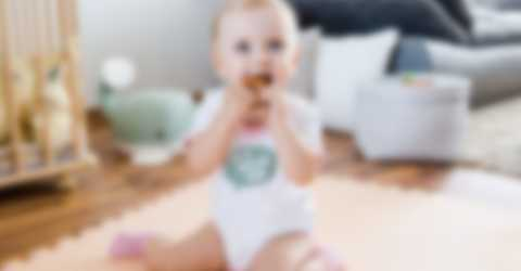 En baby leker i stua med et blidt uttrykk og bruker en egendesignet babybody