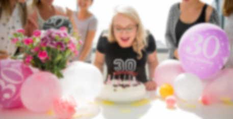 En jente blåser ut lys på bursdagskaken. Hun bruker en egendesignet T-skjorte hun har fått i gave.