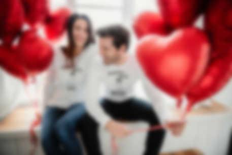 Paar stößt mit selbstgestalteten Tassen auf seine Beziehung an.