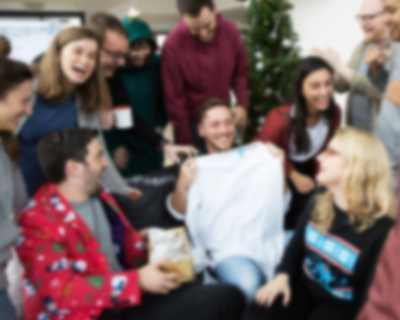 Mann hält selbst gestaltetes Langarmshirt hoch während der Weihnachtsfeier mit Kollegen
