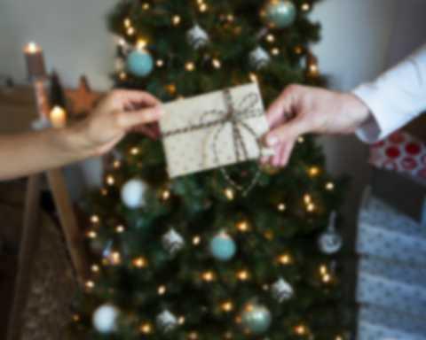 Gutschein, verpackt als Geschenk, wird vor dem Weihnachtsbaum überreicht
