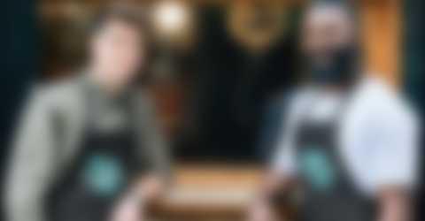 Kaksi miestä seisoo kahvilan edessä itse suunnittelemansa esiliinat yllä