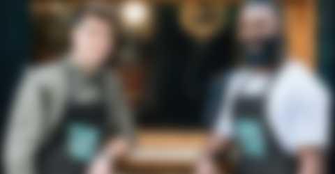 Dwaj mężczyźni stoją przed kawiarnią i mają na sobie samodzielnie zaprojektowane fartuchy