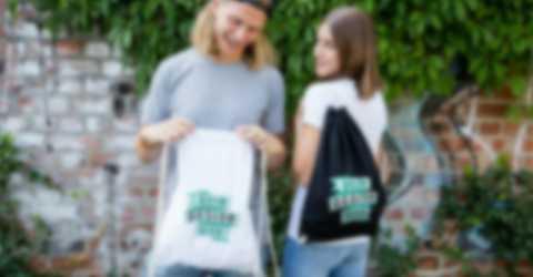 Junges Paar steht vor einer Wand und trägt selbst gestaltete Turnbeutel.