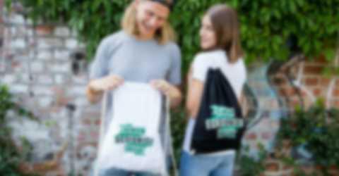 Nuori pariskunta seisoo seinän edessä itse suunniteltujen jumppapussien kanssa.