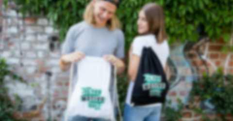 Giovane coppia davanti a una parete con una sacca sportiva personalizzata.