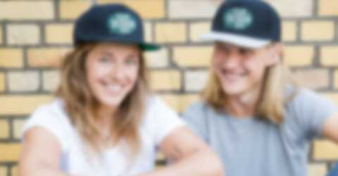 Couple sitting in front of a wall wearing personalised hats