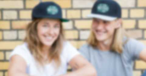 Giovane coppia seduta davanti a una parete indossa cappellini personalizzati