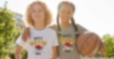 To barn poserer i egendesignede T-skjorter mens de spiller basketball